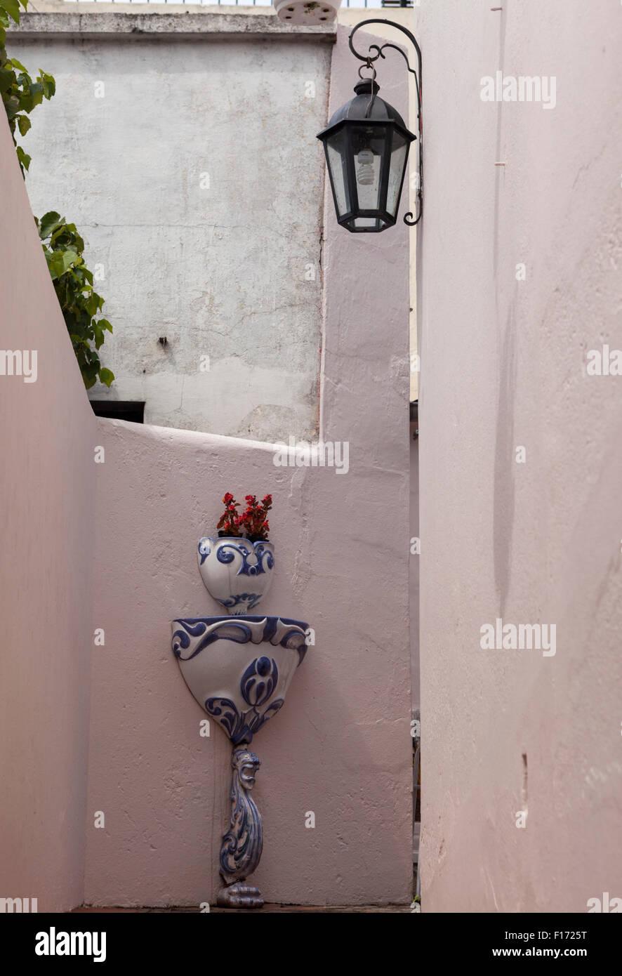 Semoir en porcelaine & fontaine sur mur dans la Calle de passage de Santa Rita dans la vieille ville de Colonia Photo Stock
