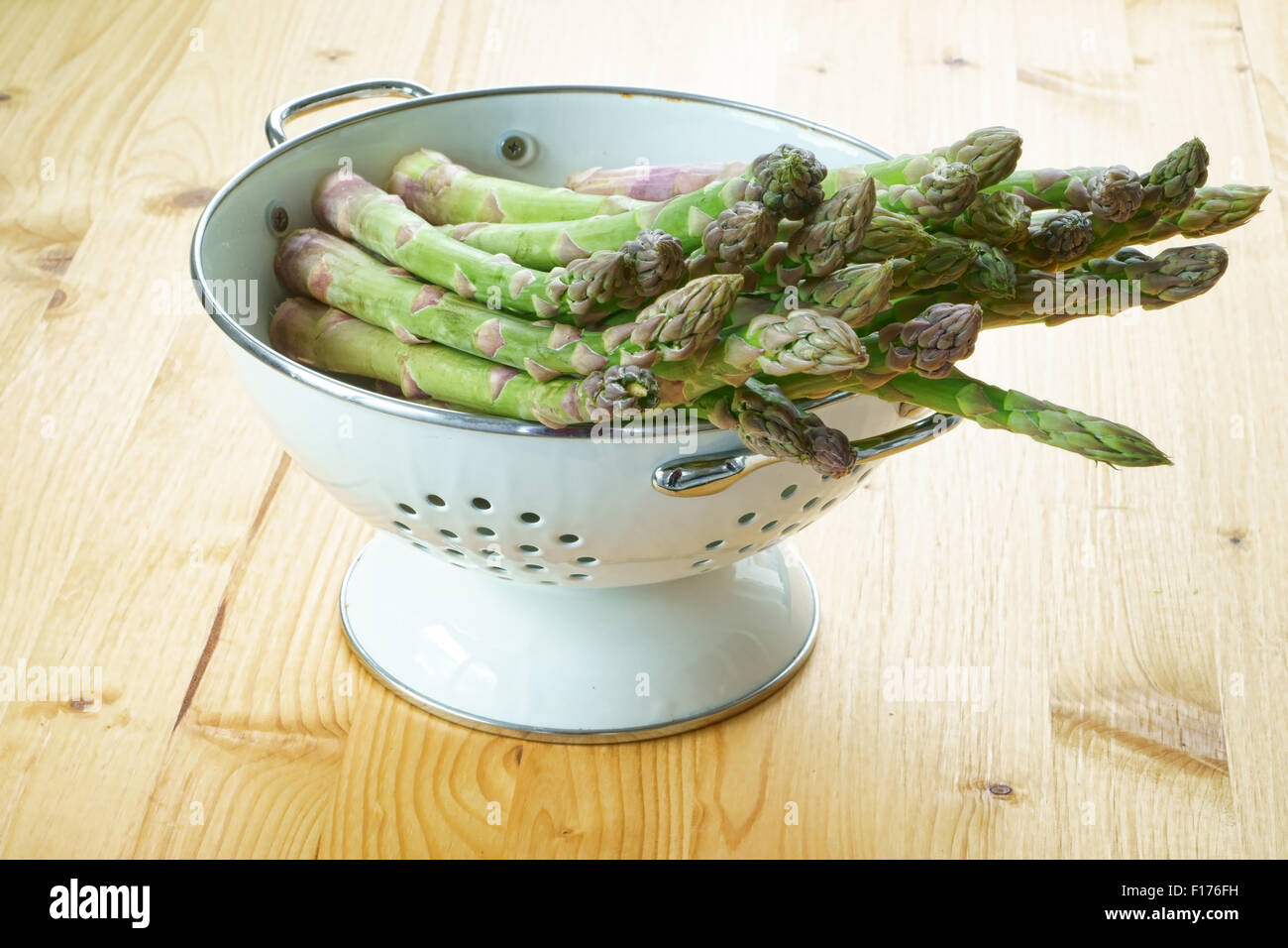 Les asperges vertes dans une passoire en émail blanc sur une table en bois rustique Banque D'Images