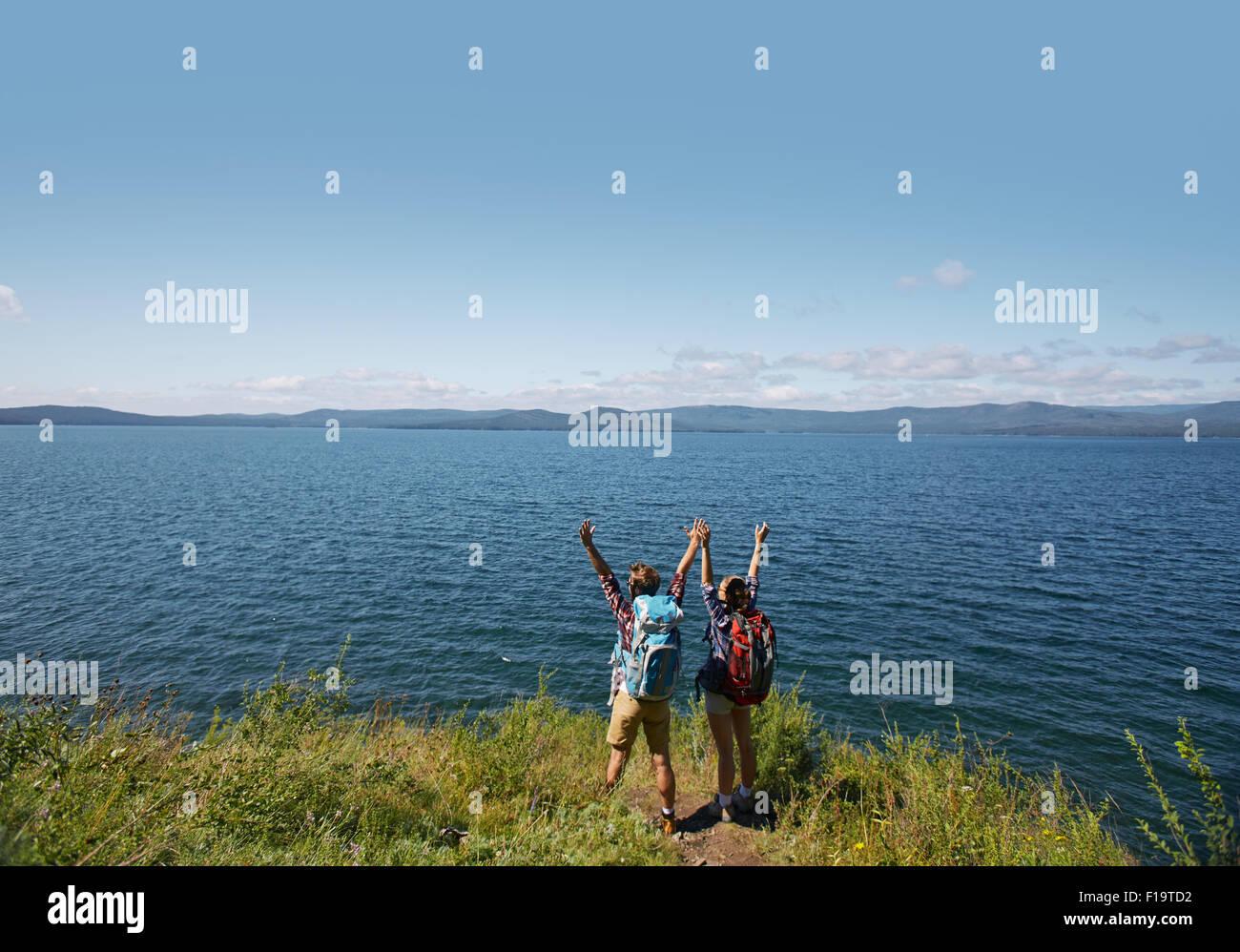 Les randonneurs extatique avec les bras levés debout près de la mer Photo Stock