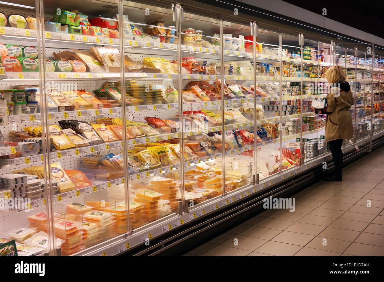 Shop assistant remplit les étagères du magasin dans l allée des produits  frais réfrigérés Photo f58eaf268dcc