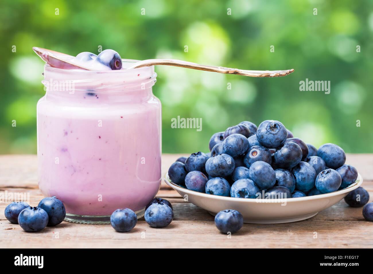Bleuets frais yogourt en pot de verre et soucoupe avec les myrtilles. Photo Stock
