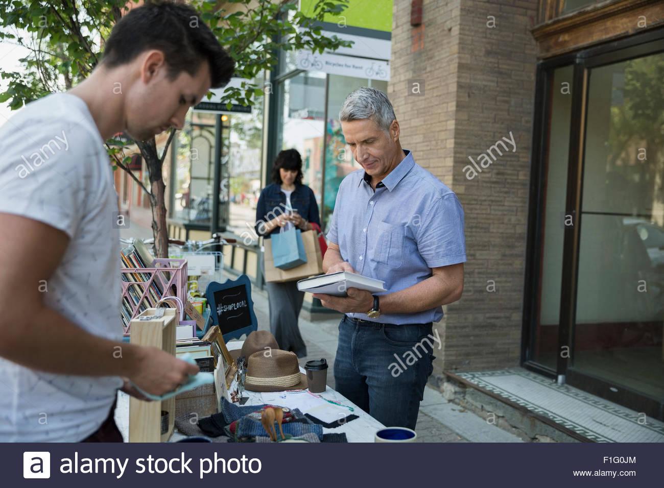 L'homme parcourt livre à vente-trottoir Banque D'Images