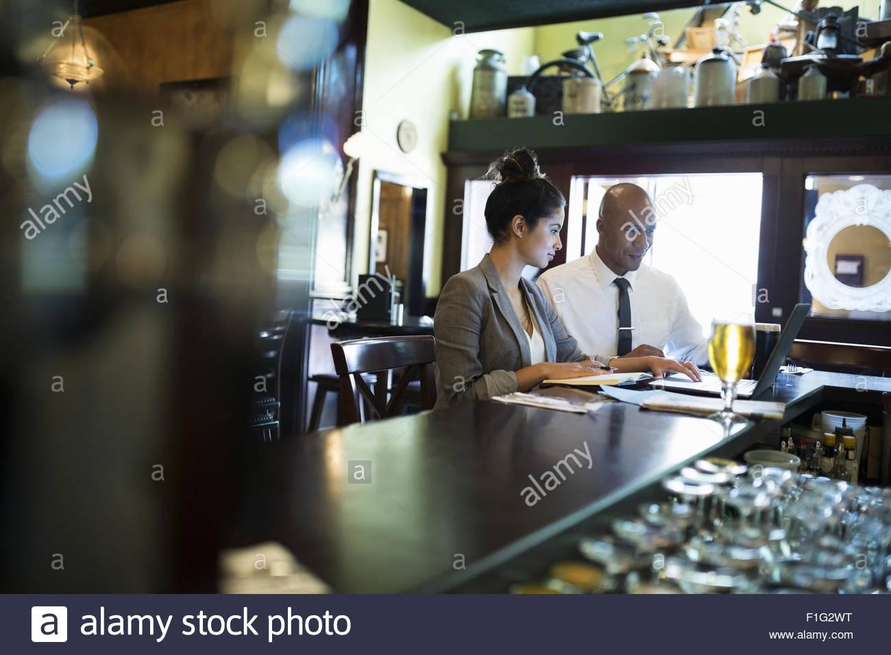 Les gens d'affaires travaillant à l'ordinateur portable dans un pub Photo Stock