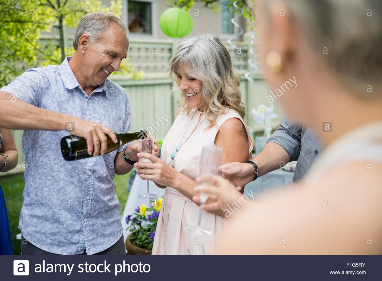 Mari pouring champagne pour femme at garden party Photo Stock