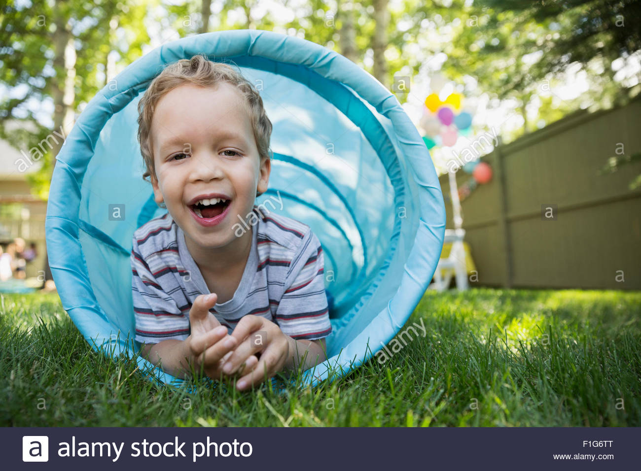 Portrait smiling boy à l'intérieur de tunnel jouet in backyard Photo Stock