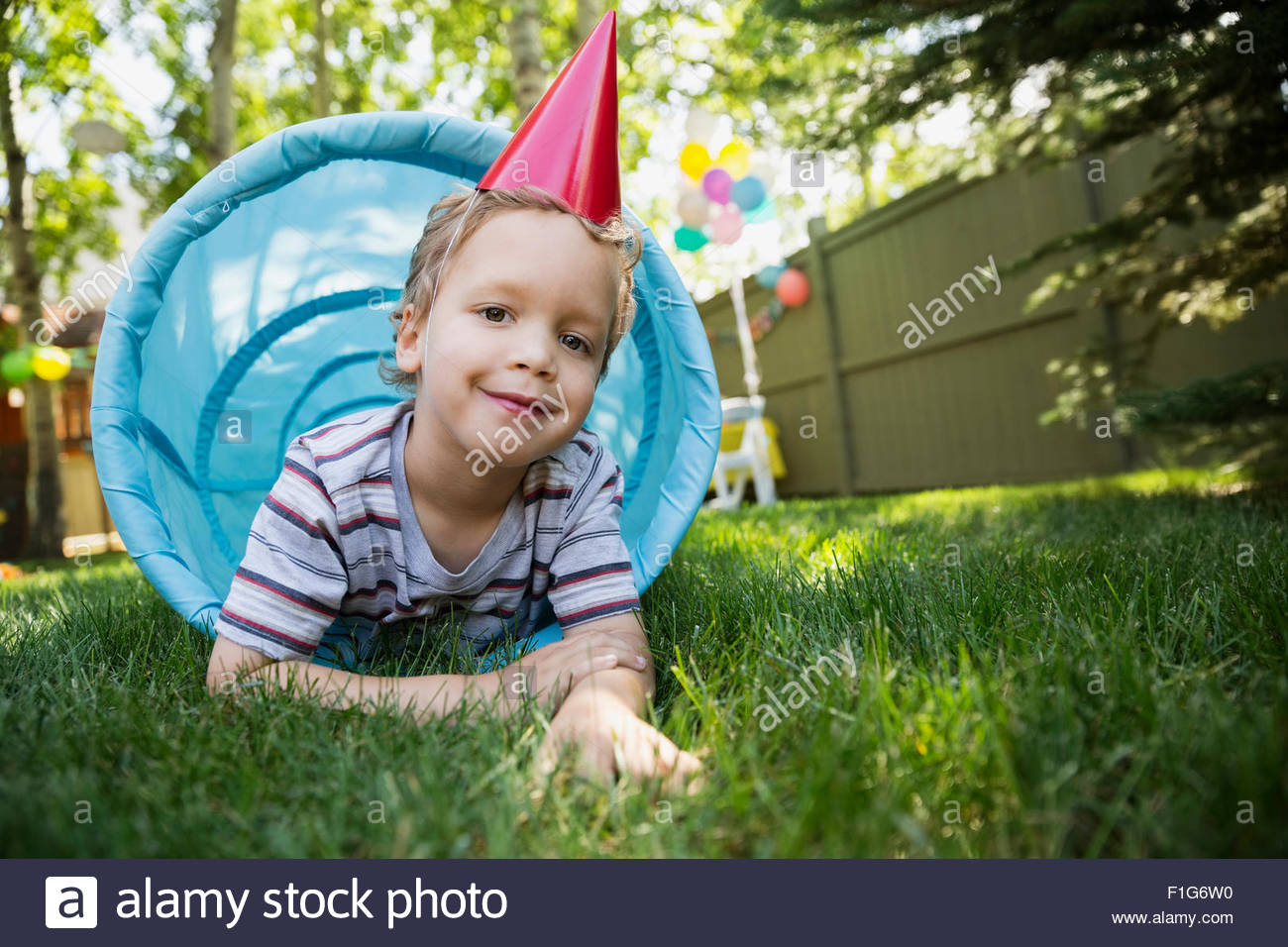 Portrait of boy wearing party hat en tunnel jouet Photo Stock