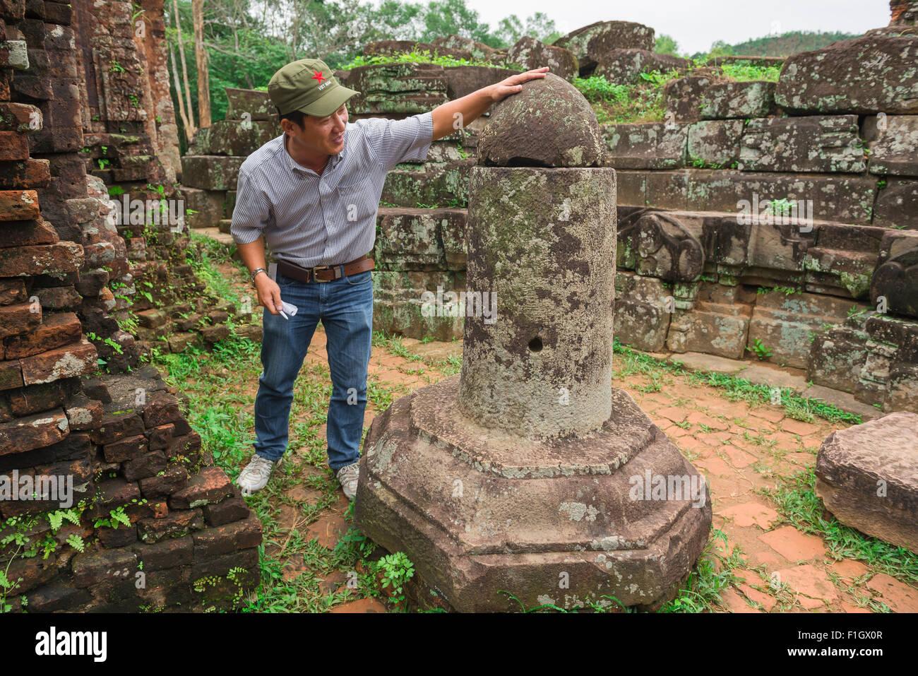 Mon fils, un guide touristique du Vietnam se trouve à côté d'un lingam en pierre à l'intérieur Photo Stock