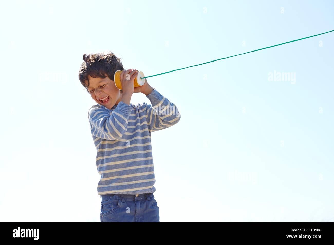 Jeune garçon, holding cup et de chaîne à l'autre téléphone Photo Stock