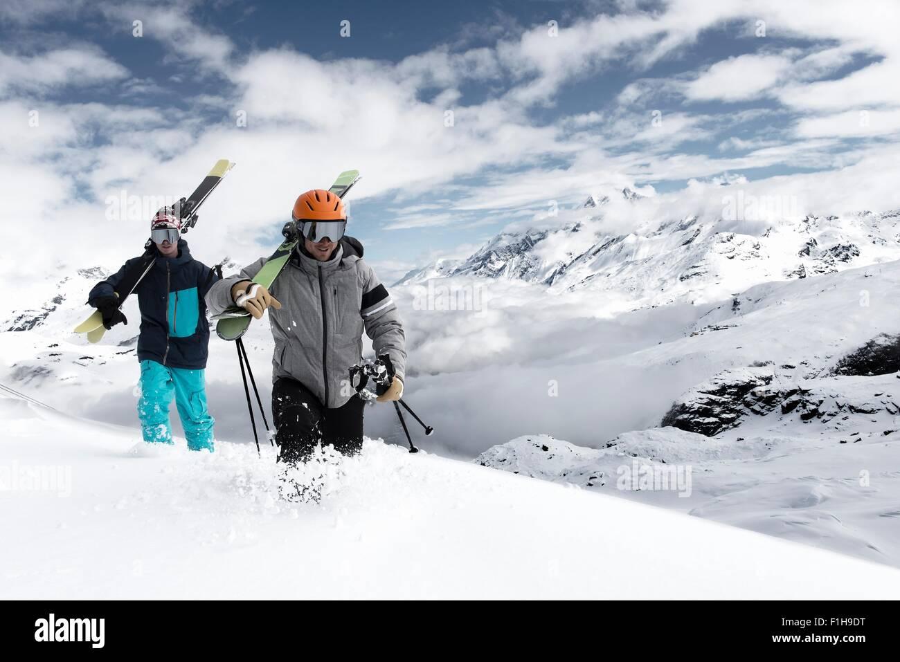 Hommes portant les skis dans la neige, Zermatt, Valais, Suisse Photo Stock