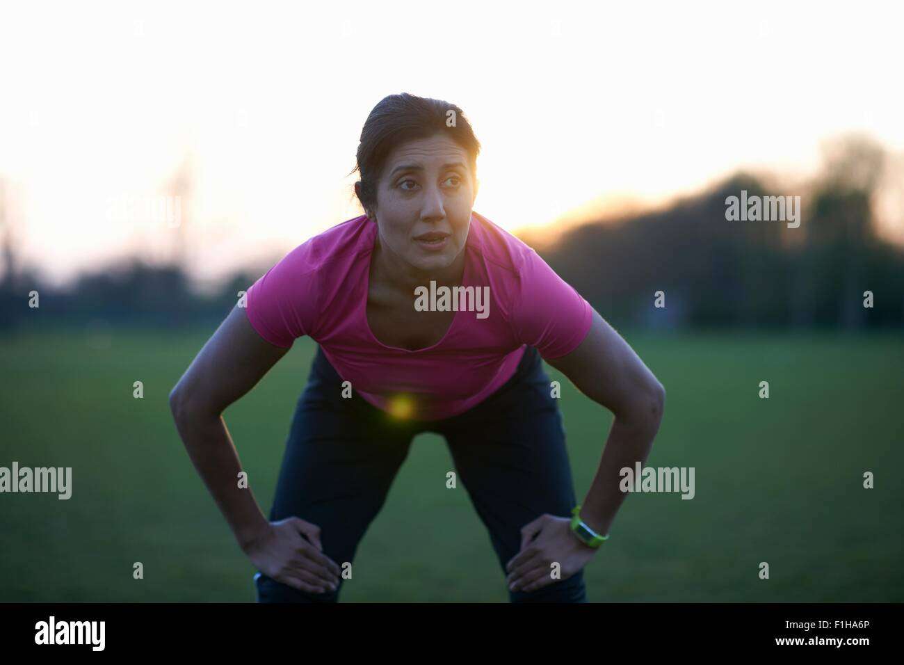 Femme mature de prendre une pause à partir de l'exercice dans park Photo Stock