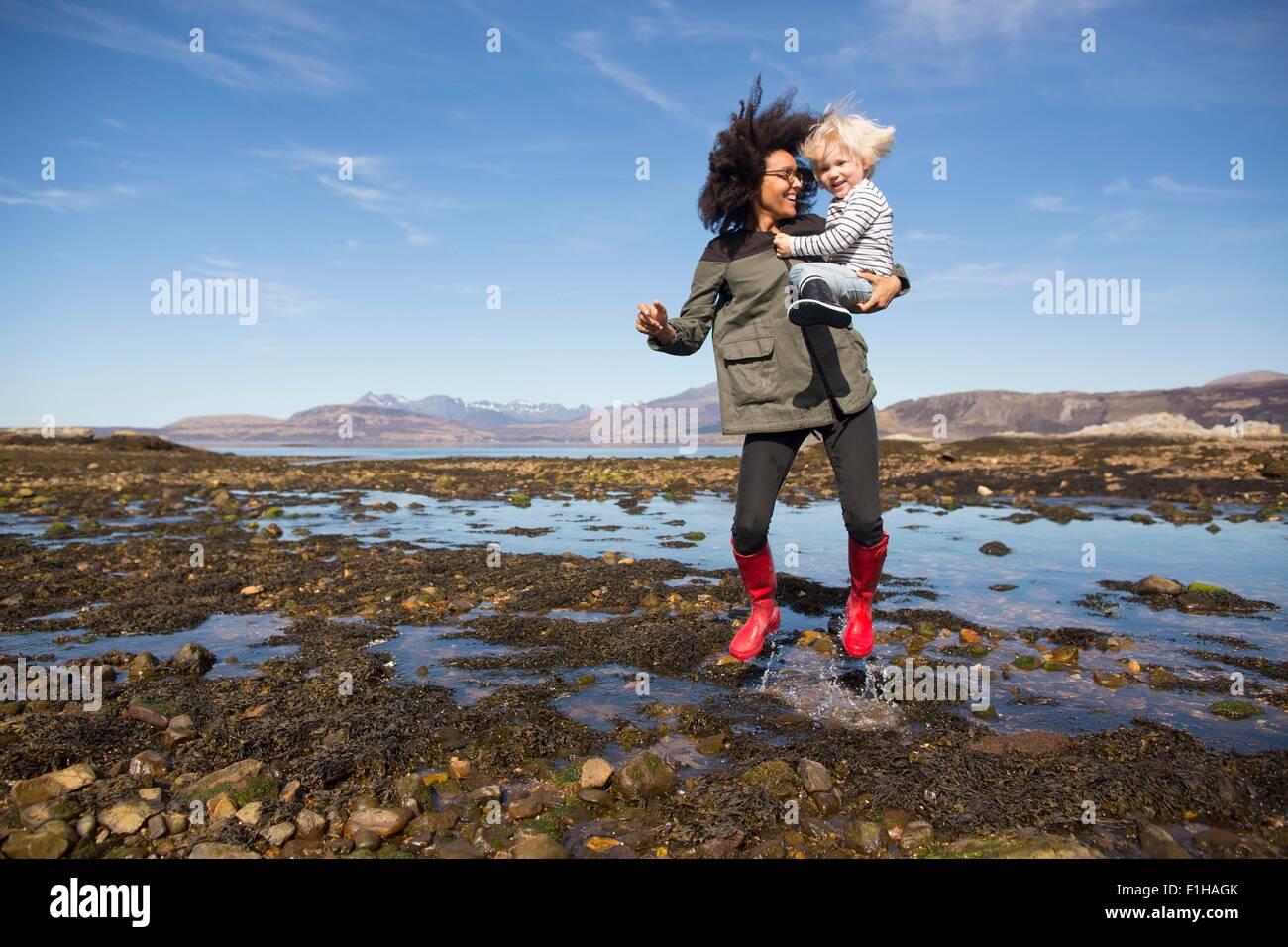 Mère tenant son Eishort saut dans le Loch, île de Skye, Hébrides, Ecosse Photo Stock