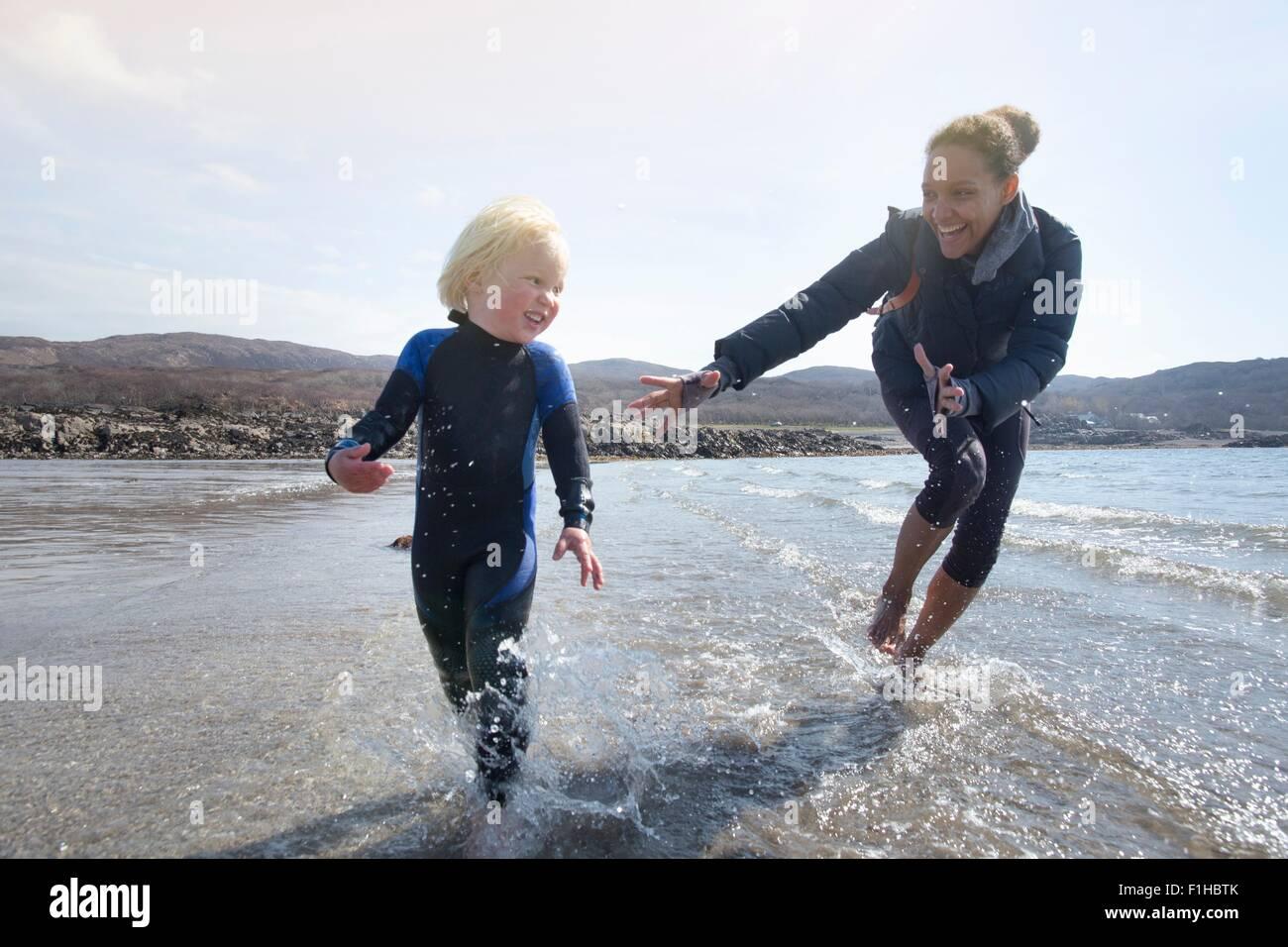 Mère et fils s'exécutant sur plage, Loch Eishort, île de Skye, Hébrides, Ecosse Banque D'Images