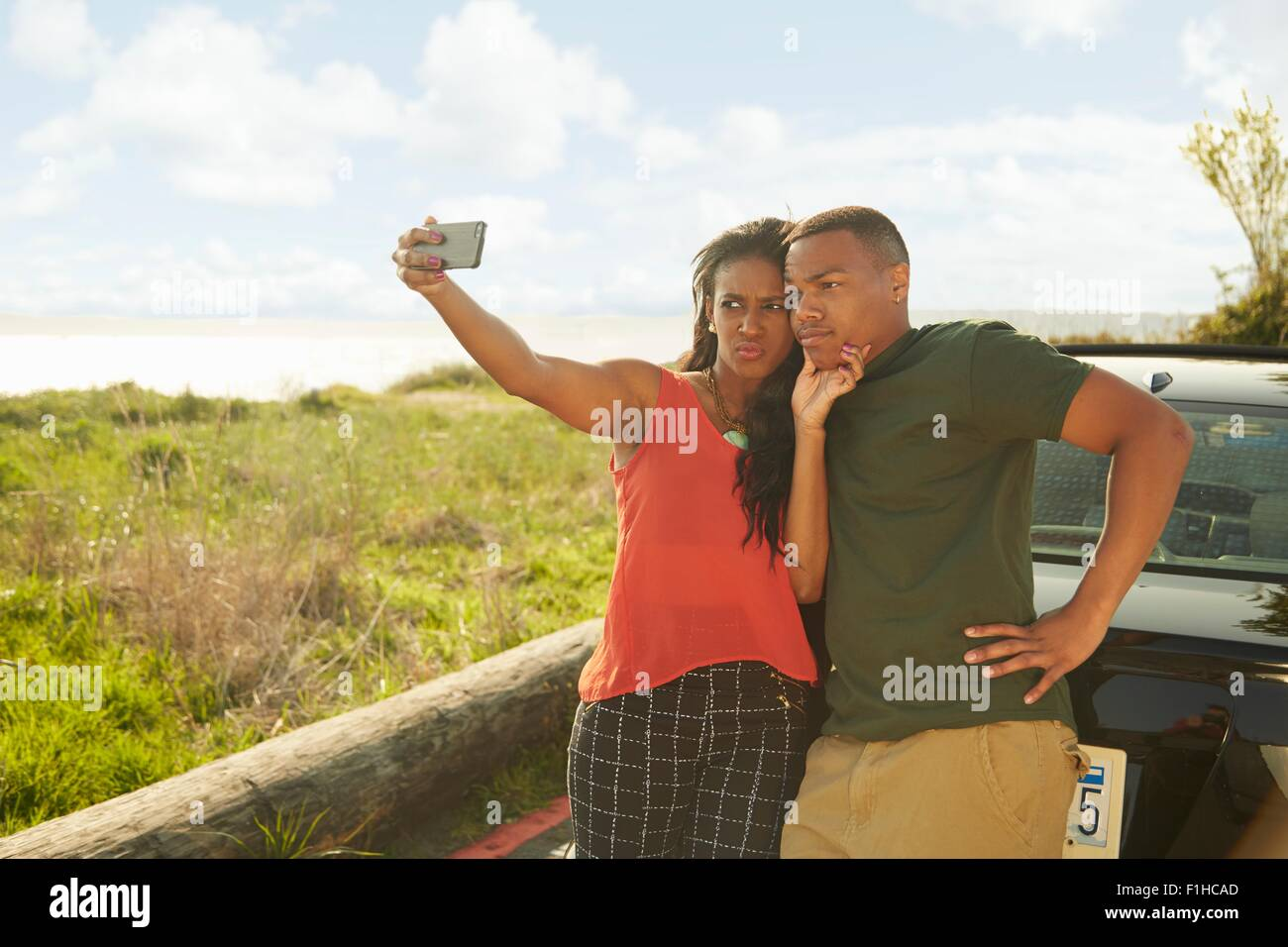 Jeune couple using smartphone, en tenant, selfies making faces Photo Stock