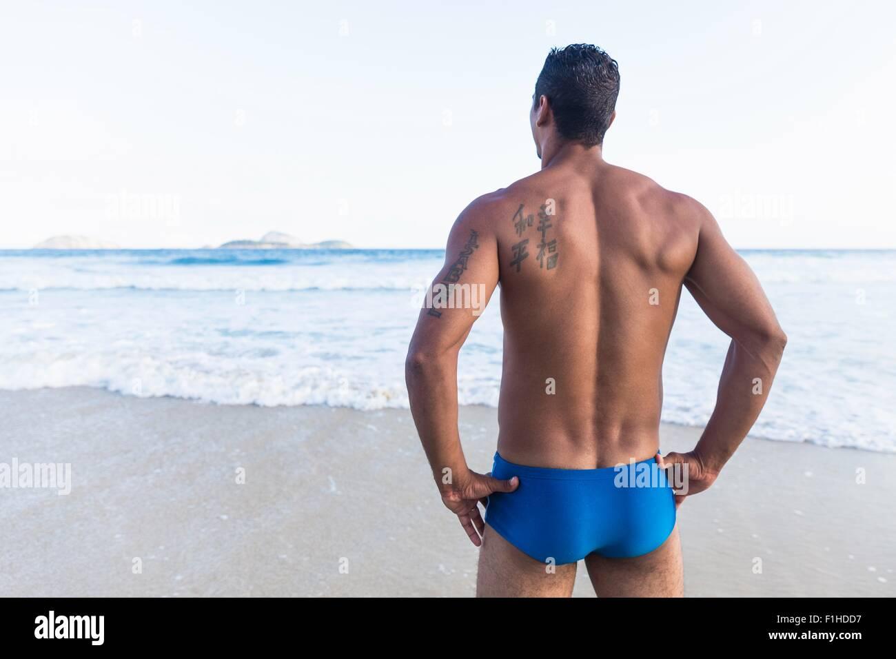 Mid adult man wearing maillot de bain, donnant sur la mer, vue arrière Photo Stock