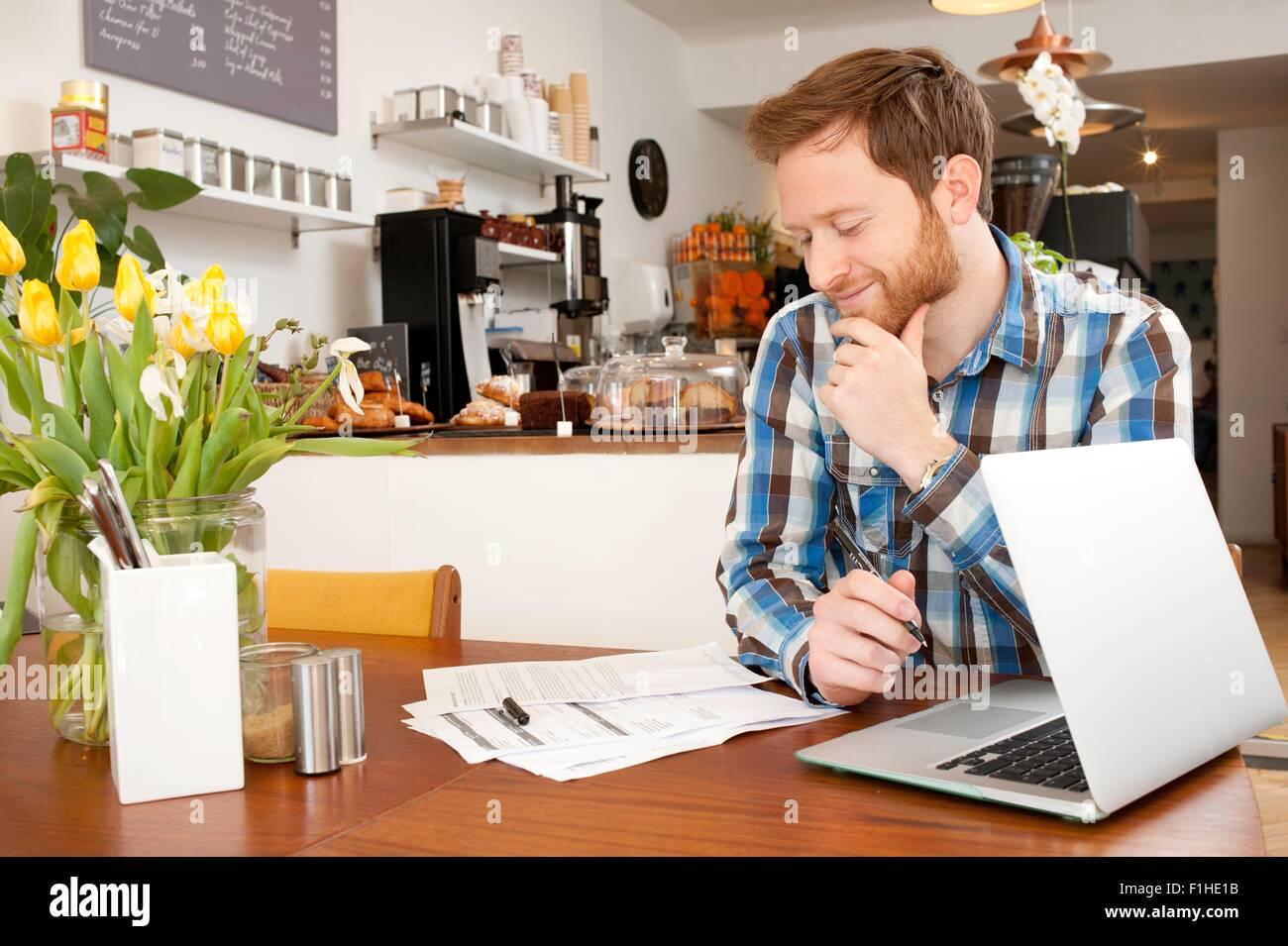 La clientèle masculine en remplissant le formulaire de demande en cafe Photo Stock