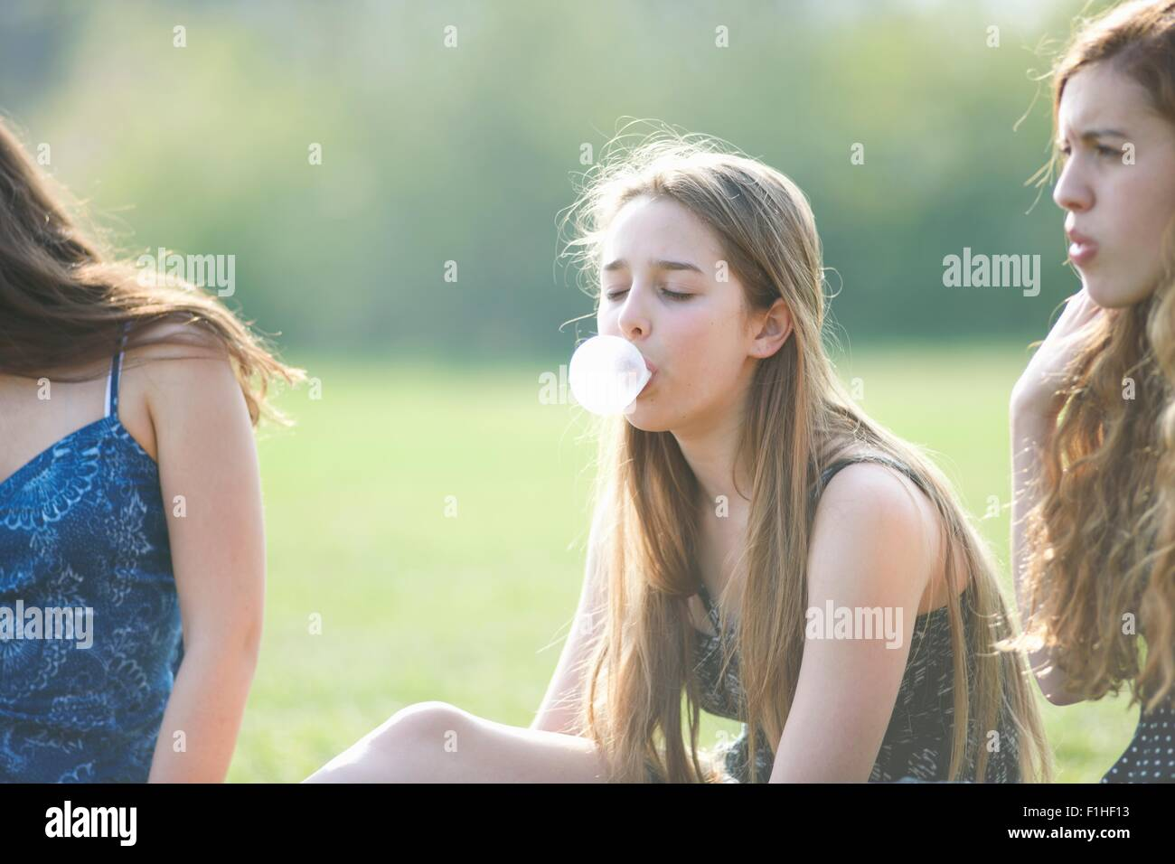 Woman blowing bubble gum bubble in park Photo Stock