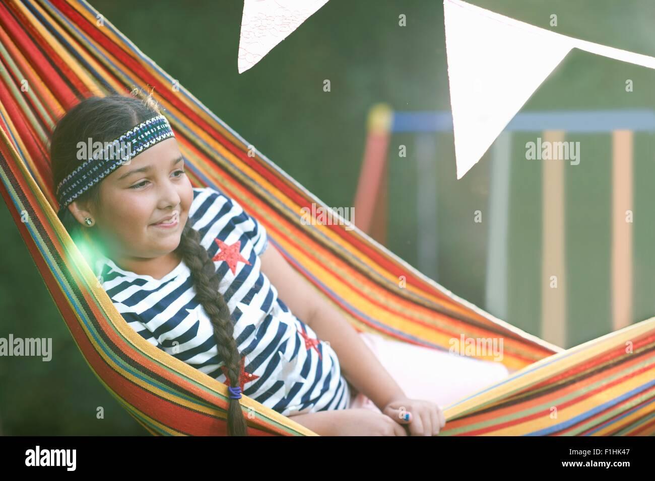 Portrait de fille mignonne avec bandeau et fuseaux repose dans le jardin Hamac rayé Photo Stock