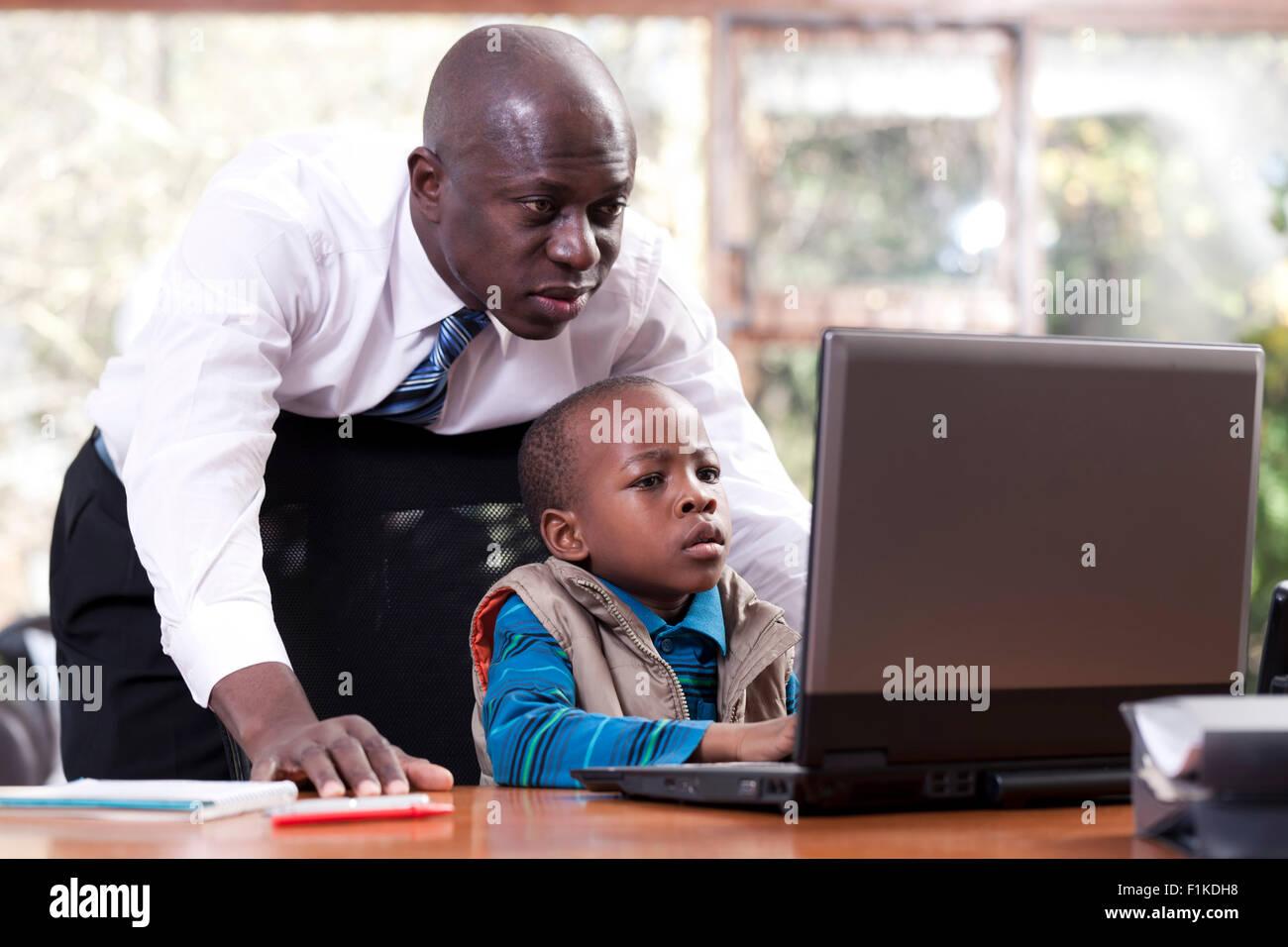 Un jeune garçon est assis de l'Afrique chez son père 24, jouant sur un leptop tandis que son père veille sur son Banque D'Images