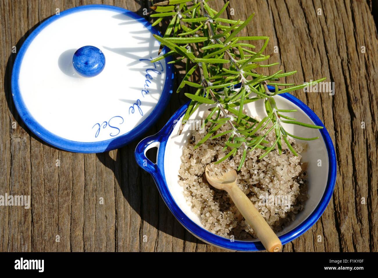 Petit plat en porcelaine de fleur de sel et une branche de romarin sur une table en bois rustique Photo Stock