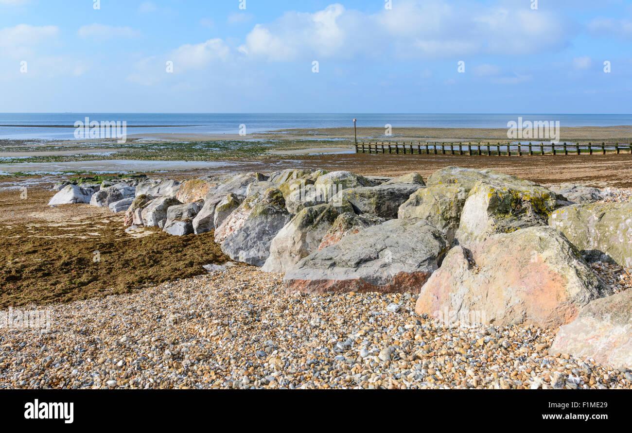 De gros rochers sur une plage de galets au bord de la mer. Photo Stock