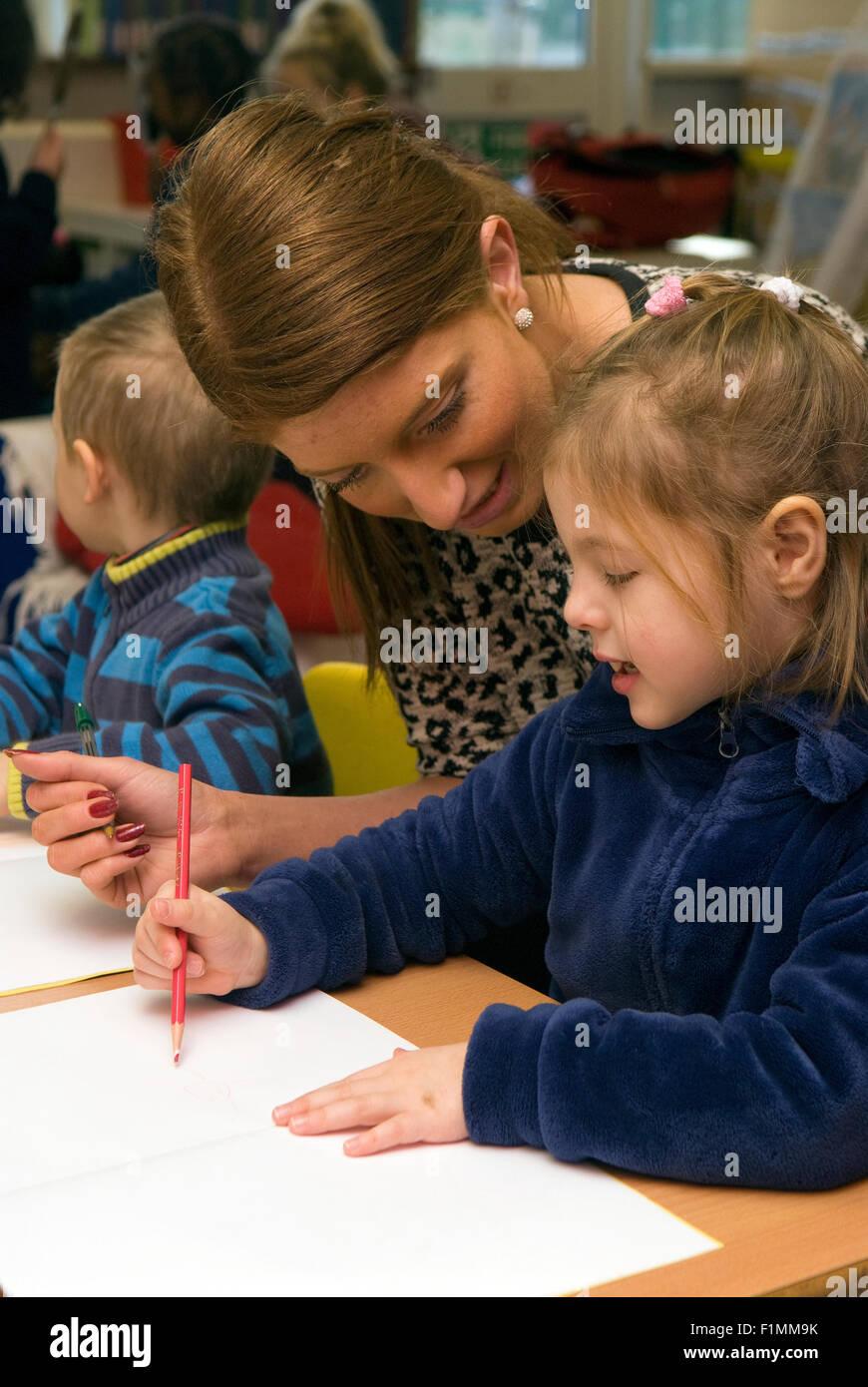 Primary school teacher assisting élève en classe, Londres, Royaume-Uni. Photo Stock