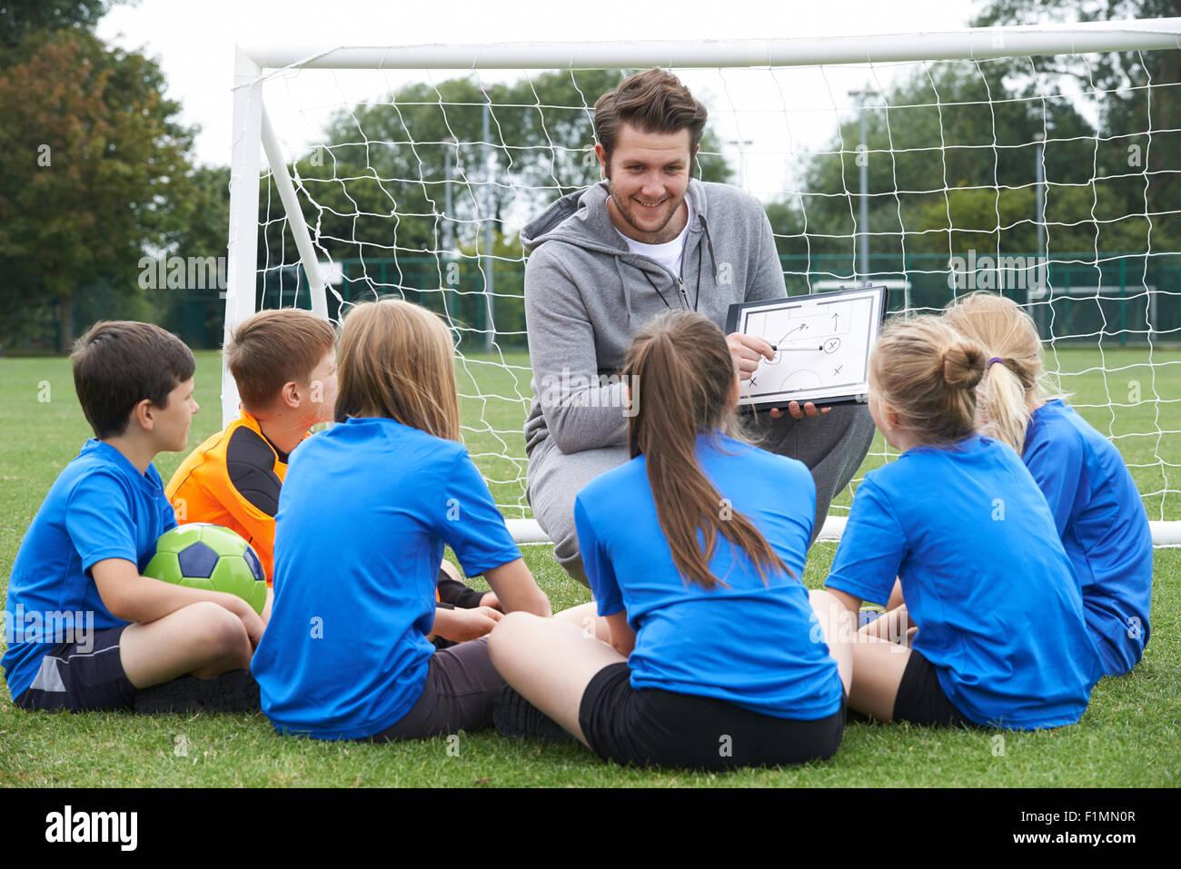 Coach de l'équipe donnant parler à l'équipe de soccer de l'école élémentaire Photo Stock