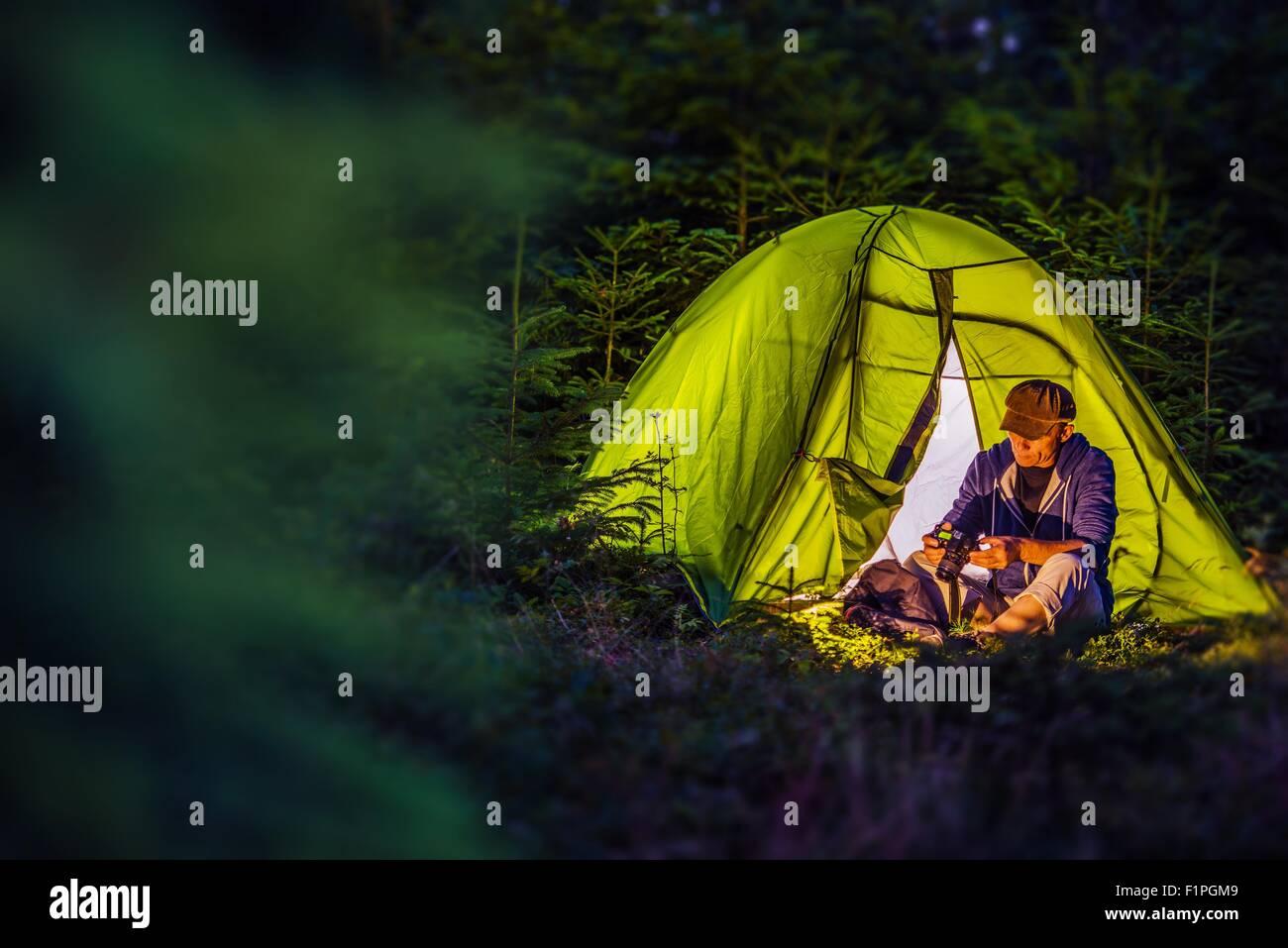 Camping de la forêt la nuit. L'âge moyen Caucasian Hiker avec son appareil photo numérique et Photo Stock