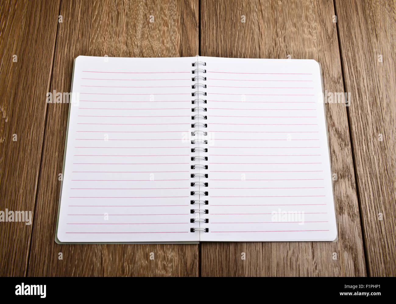 Feuilles de carnet. Page blanche sur fond de bois Photo Stock