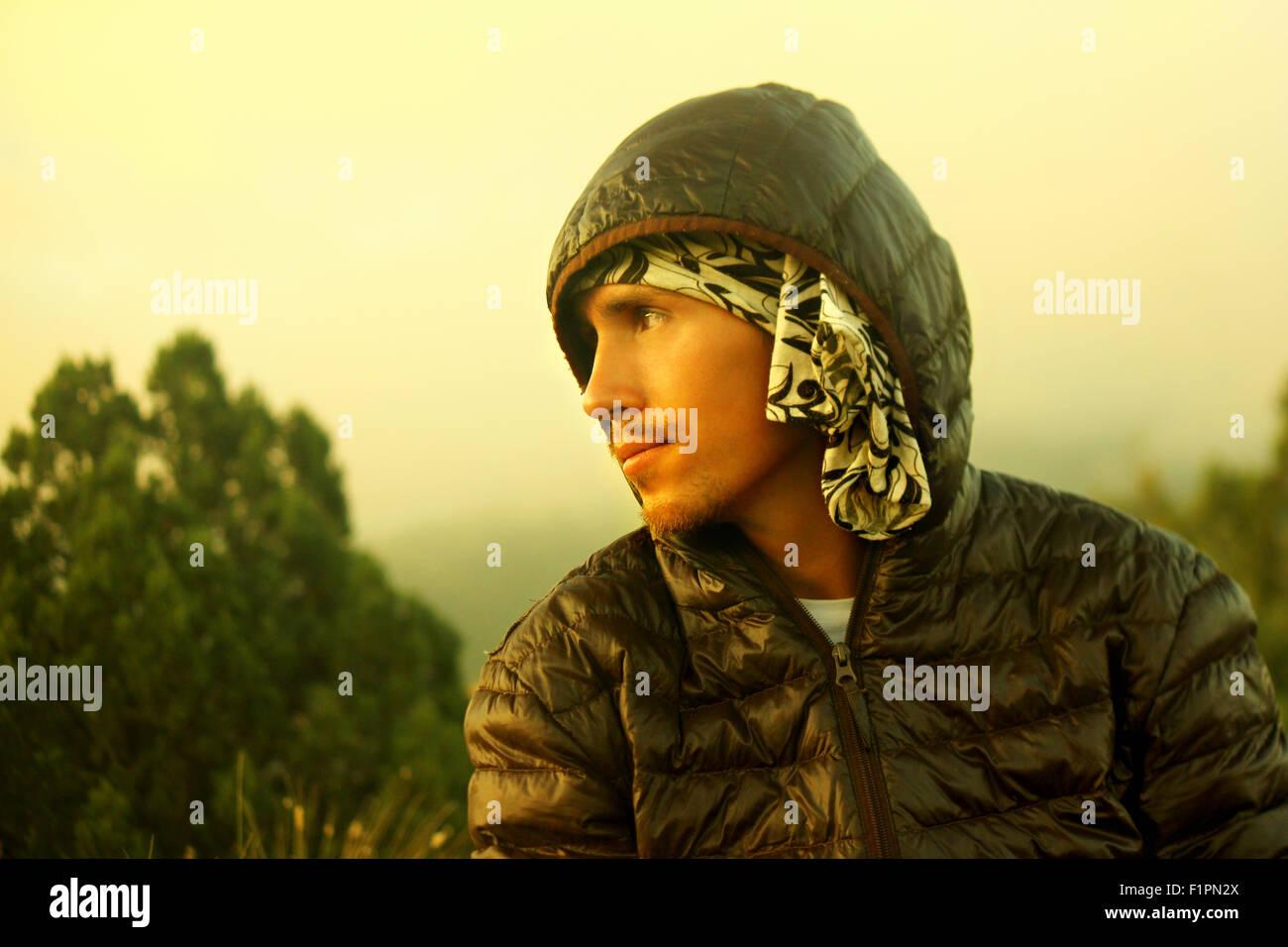 Young handsome man with beard en automne veste sombre vers le bas à capuchon dans la nature regarde ailleurs. Photo Stock