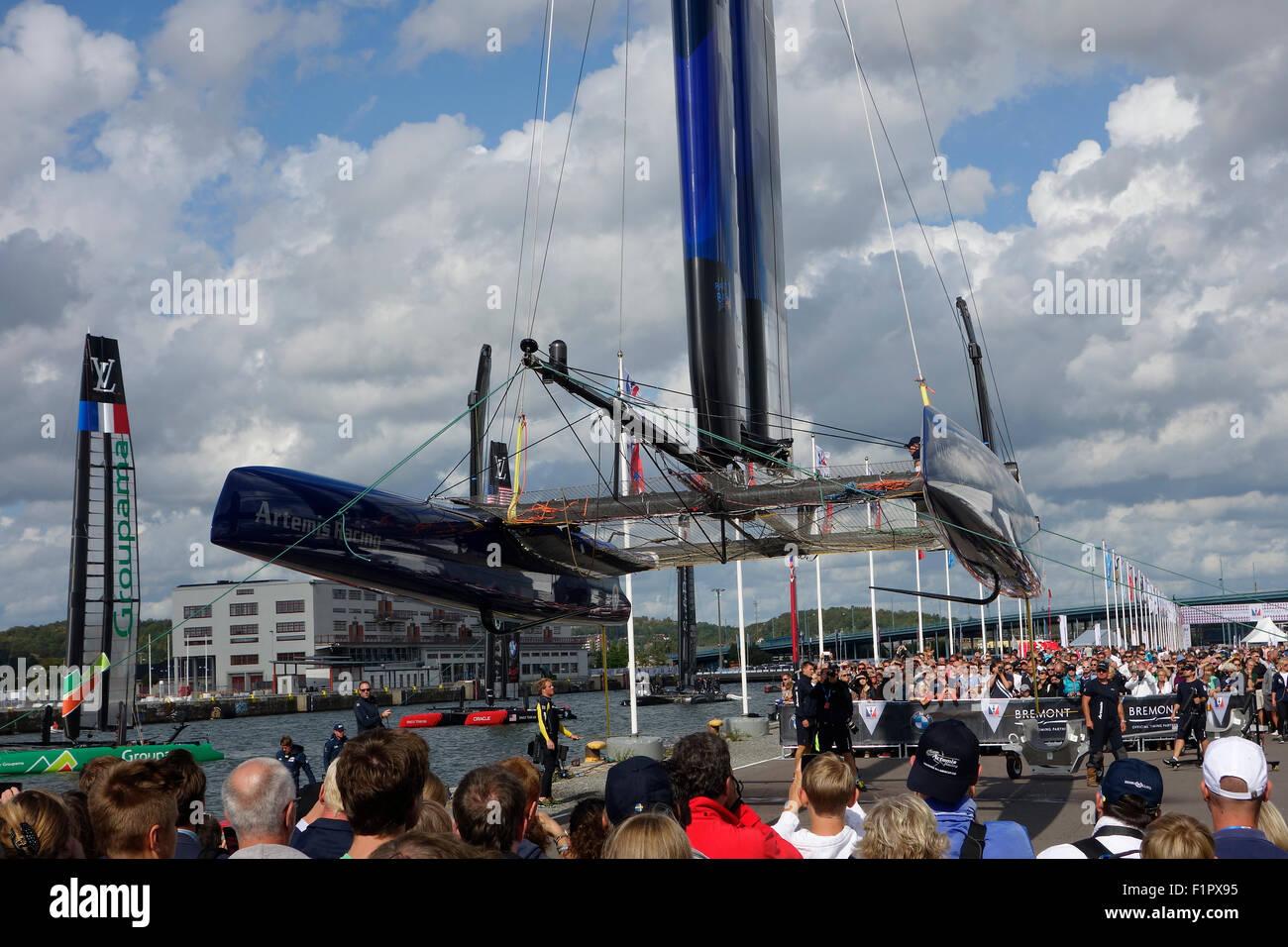 Les gens se rassemblent et se saisir de l'occasion de voir Swedish America's Cup 72 catamaran de classe ci-dessous lorsqu'il est soulevé pour la voile aile r Banque D'Images