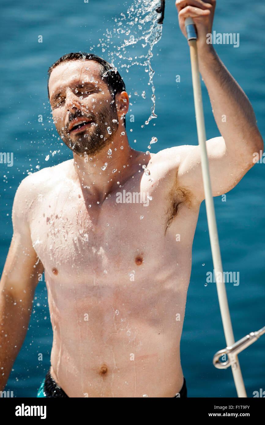 Jeune homme de prendre une douche sur voilier, Mer Adriatique Photo Stock