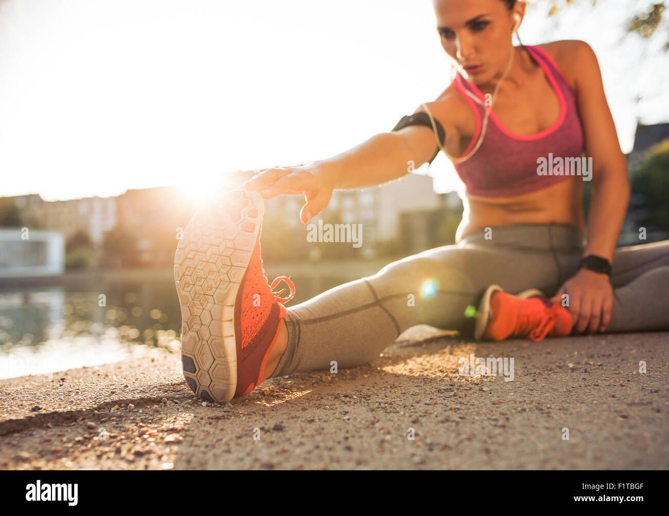Jeune femme runner stretching jambes avant de faire son entraînement d'été. La sportive de préchauffage Photo Stock