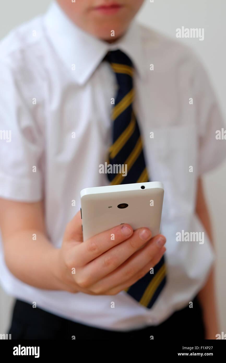 Un écolier en uniforme en utilisant son téléphone mobile ( texto ) UK Photo Stock