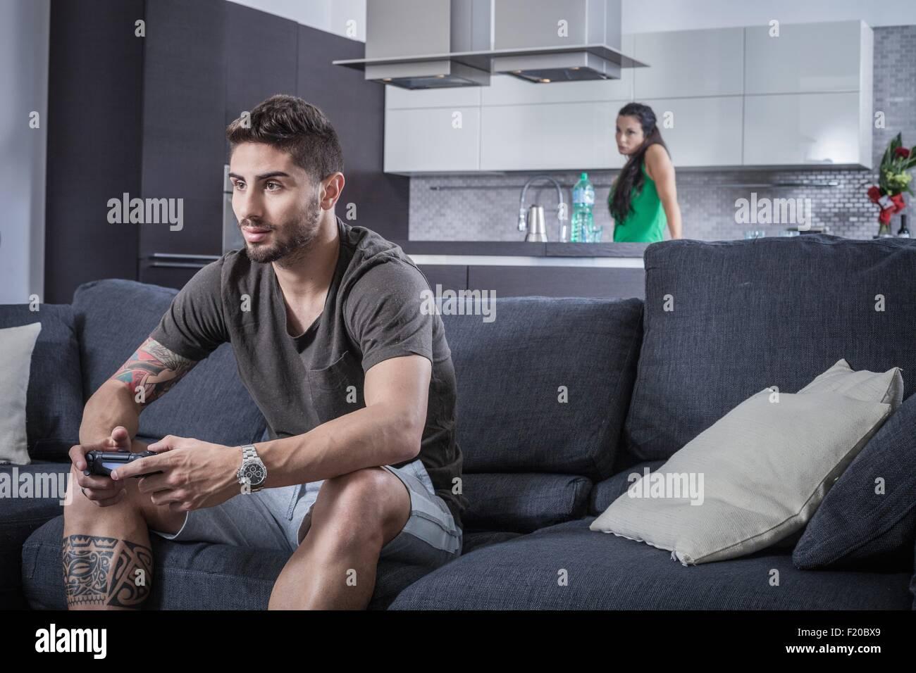Jeune homme sur canapé à l'aide de contrôle de jeu vu par petite amie en colère Photo Stock
