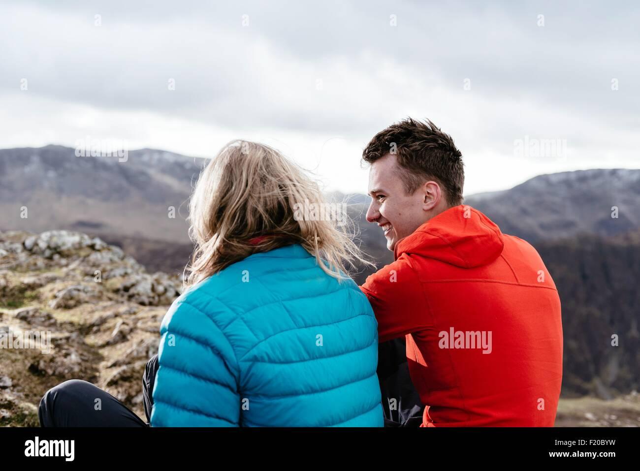 Jeune couple assis sur une colline, vue arrière, Keswick, Lake District, Cumbria, Royaume-Uni Photo Stock