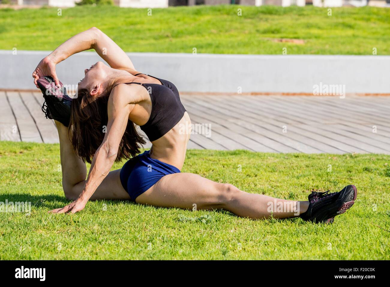 Young woman doing stretches in park Photo Stock