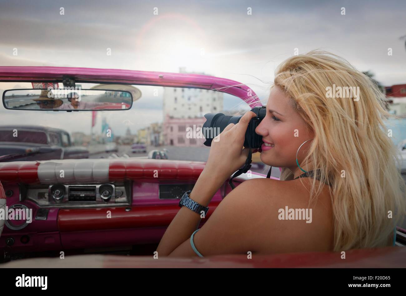 Jeune femme à prendre des photos à partir d'une voiture d'époque sur le Malecon de La Havane, Photo Stock