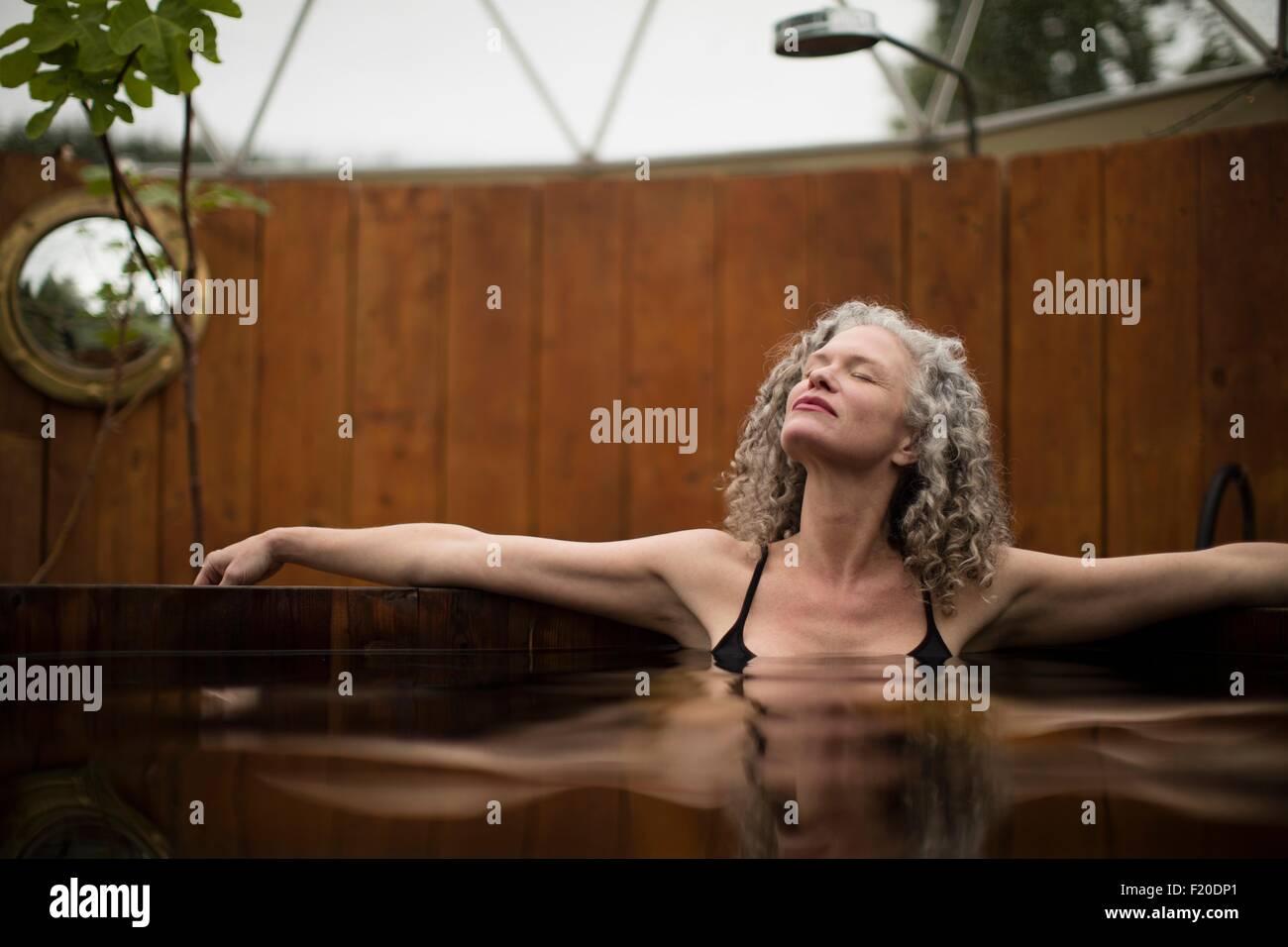 Femme mature de vous détendre dans le bain à remous de l''eco retreat Photo Stock