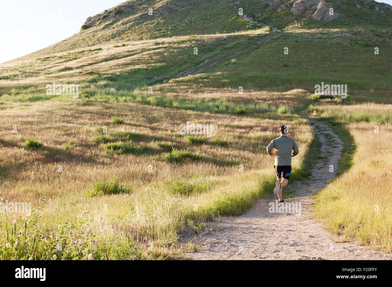 Vue arrière du jeune homme runner fonctionnant jusqu'hillside voie Photo Stock