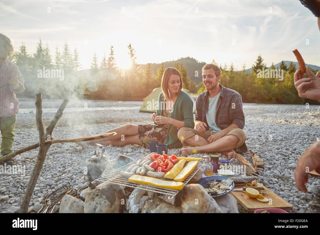 Camp famille assis autour de la cuisson des aliments sur un barbecue Photo Stock