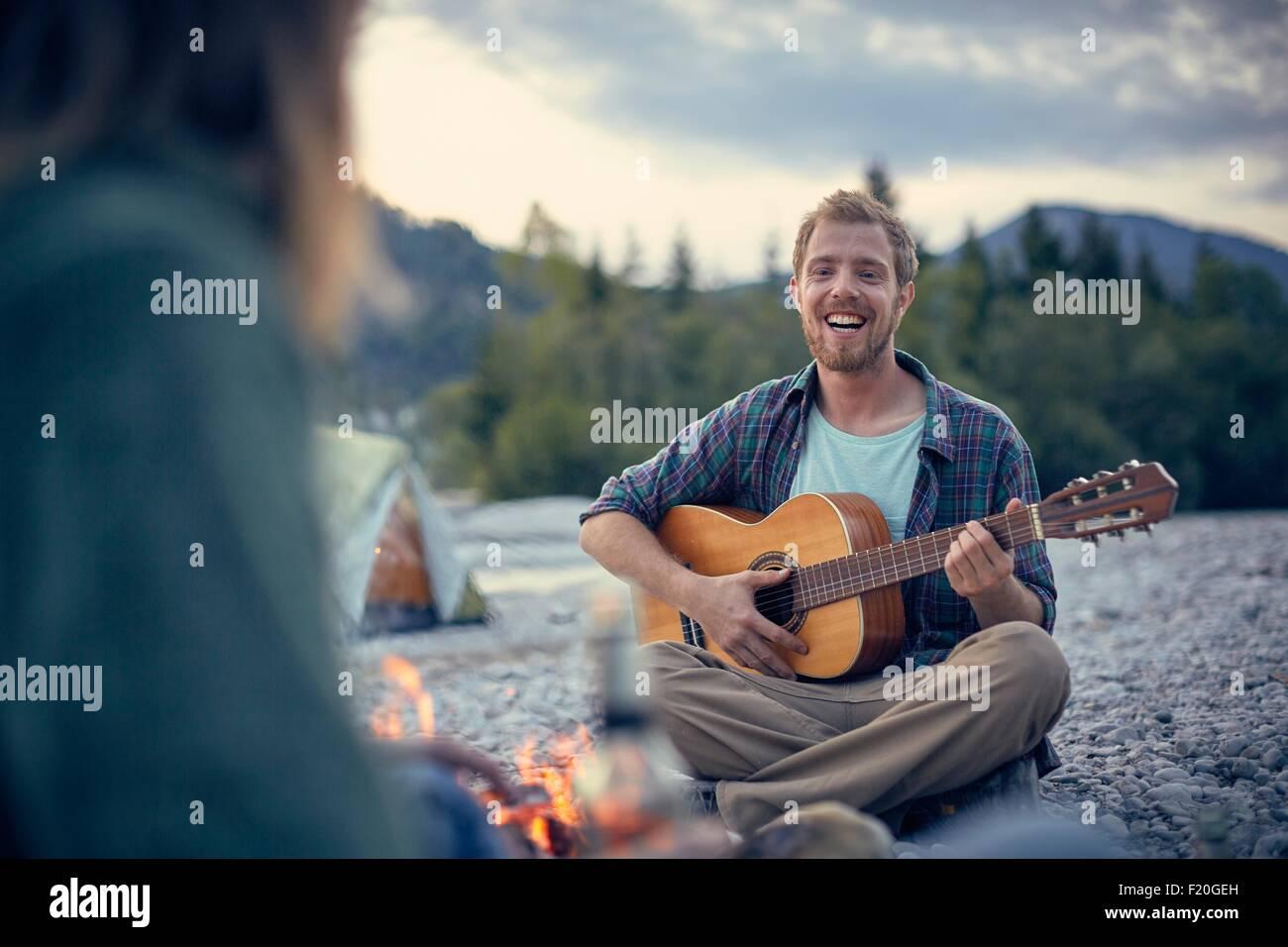 Vue avant du jeune homme assis en jouant de la guitare de feu de camp Photo Stock