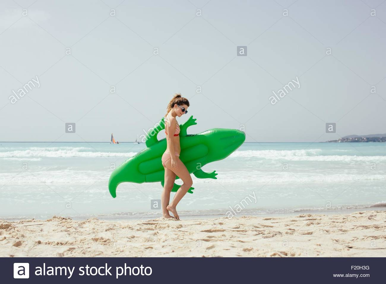 Young woman wearing bikini portant sur crocodile gonflable beach Photo Stock