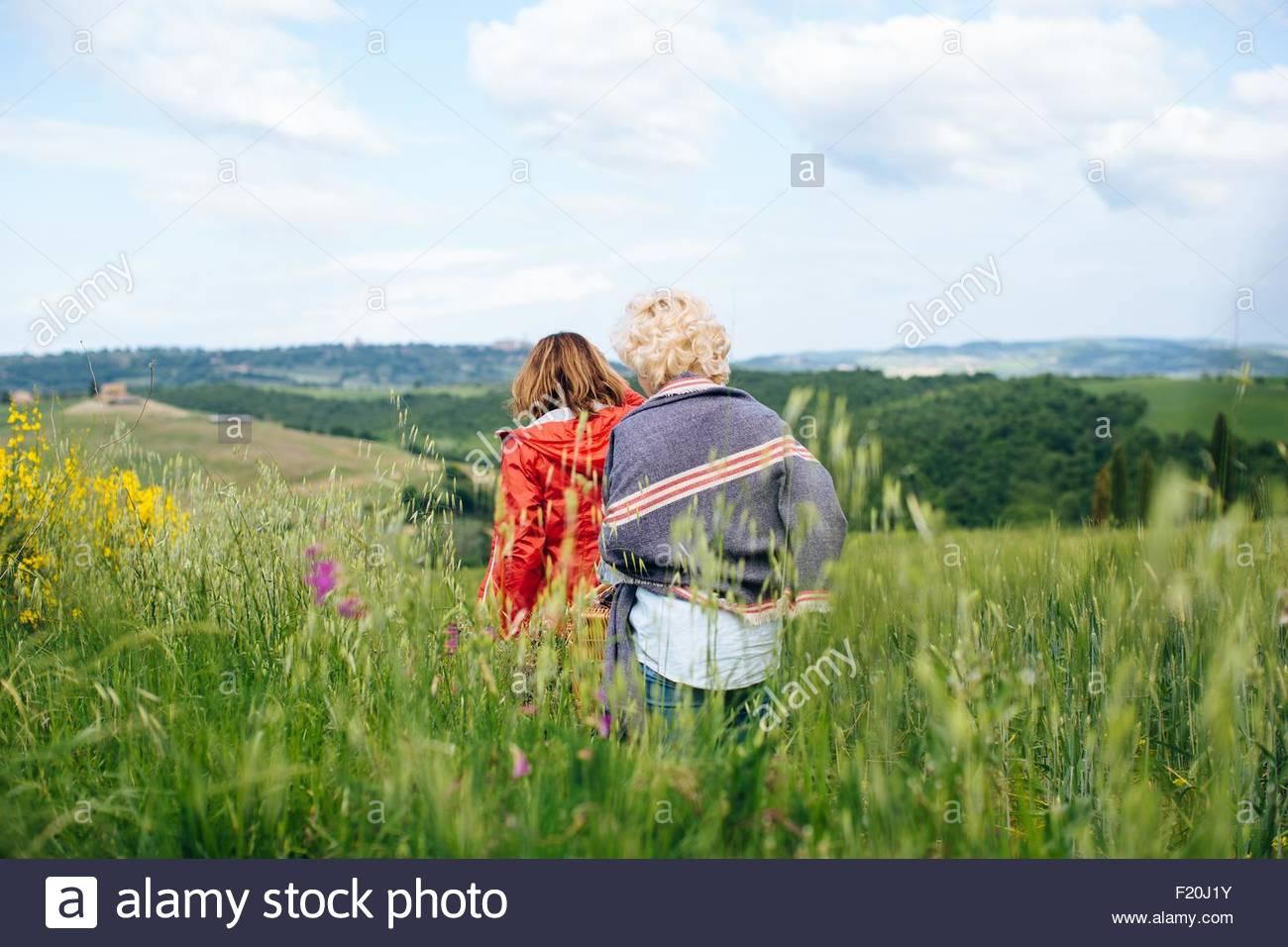 Vue arrière des deux femmes mûres se promener en wheatfield, Toscane, Italie Photo Stock