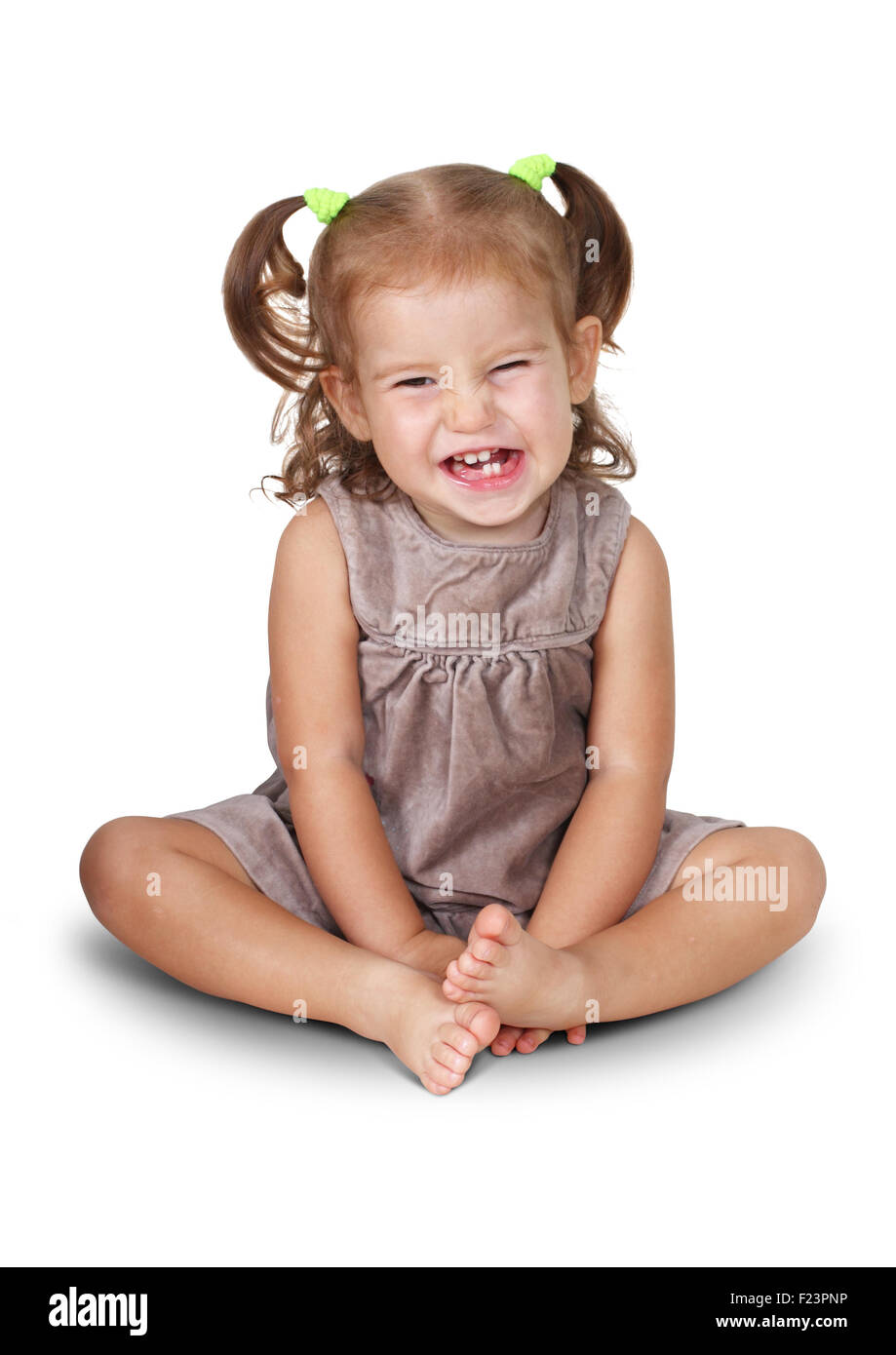 Fille enfant en colère assis avec grin isolated on white Photo Stock