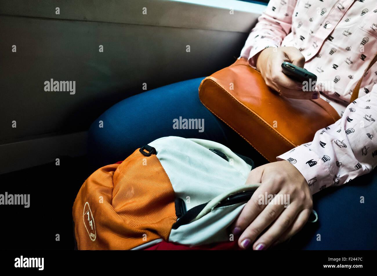 Gros plan d'une femme dans le bus de la navigation Internet sur son smartphone Photo Stock