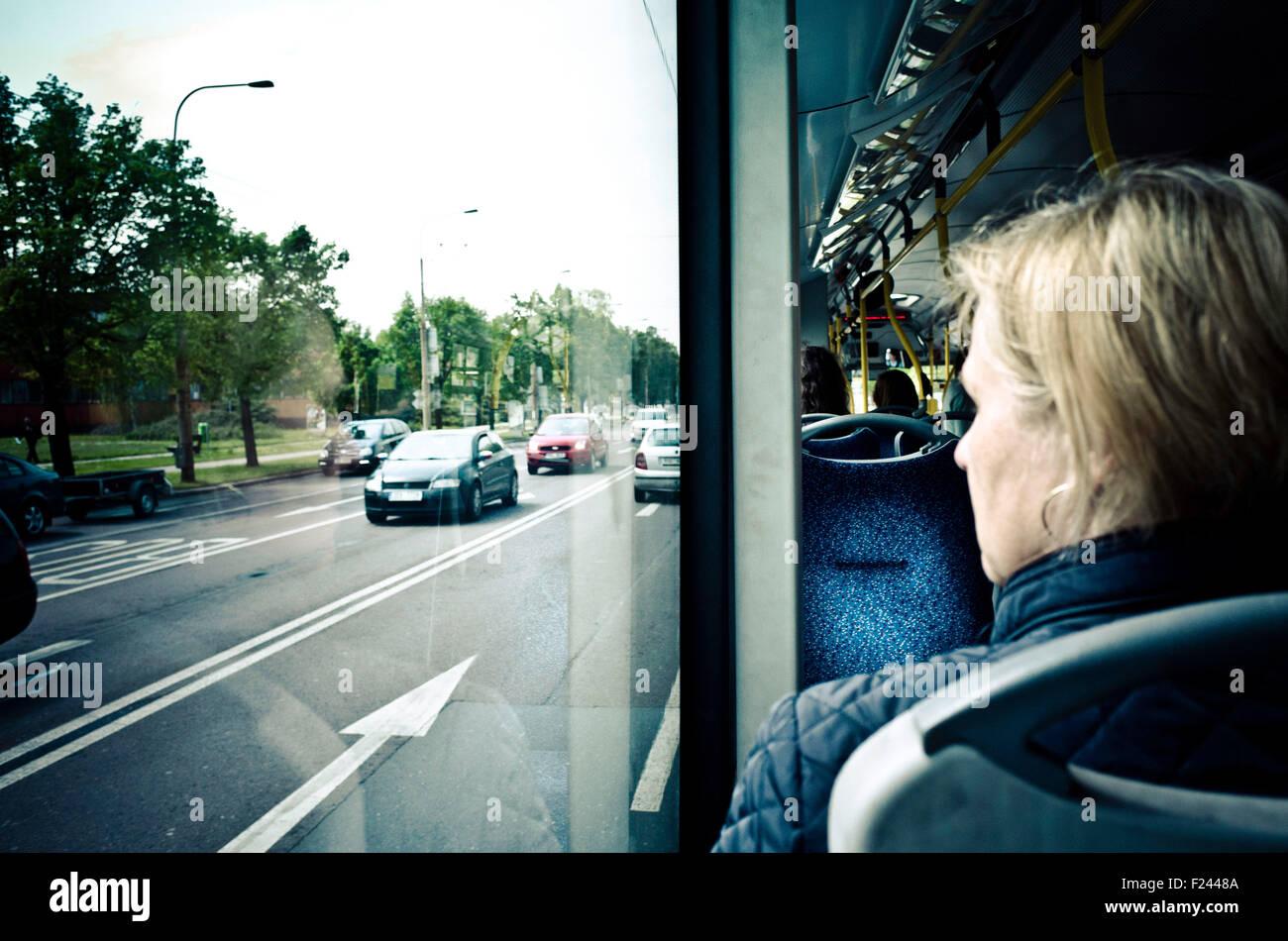 Femme en ville à la recherche de bus par la fenêtre sur des voitures sur la route Photo Stock