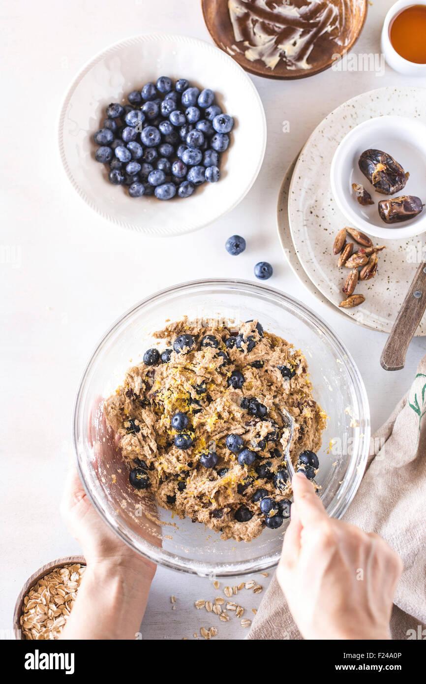 Les bleuets sont mélangés dans la pâte pour le petit déjeuner des scones. Photo Stock