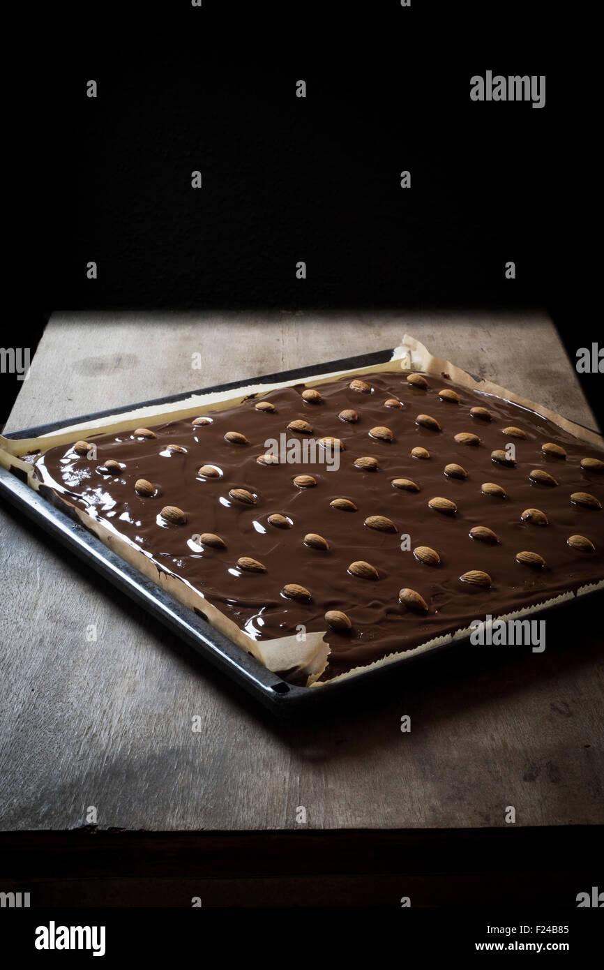 Le bac d'épices fraîchement étalé avec enrobage de chocolat et amandes sur le dessus de Photo Stock