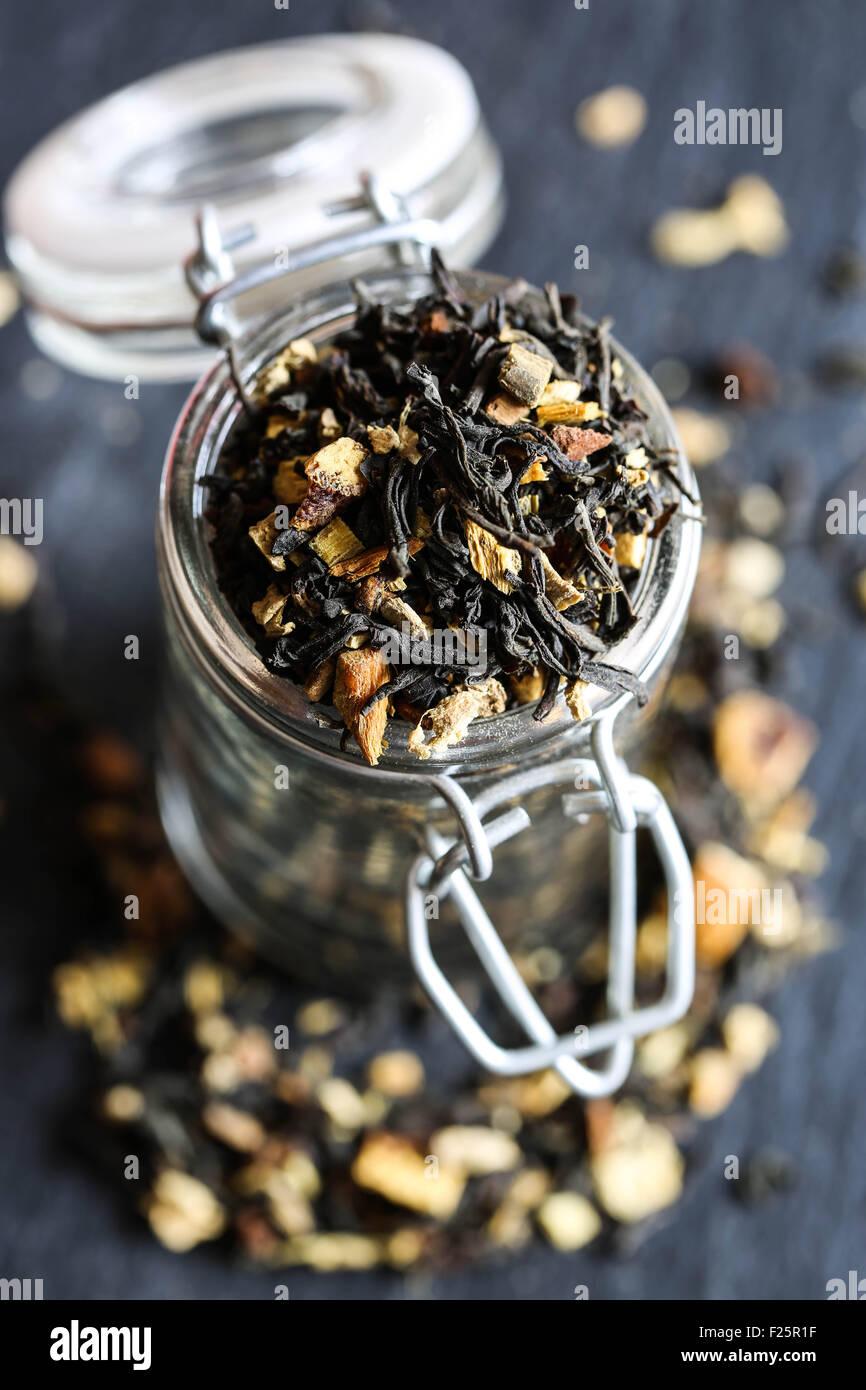 Thé noir d'inde avec orange, et les épices dans un pot de verre. Photo Stock