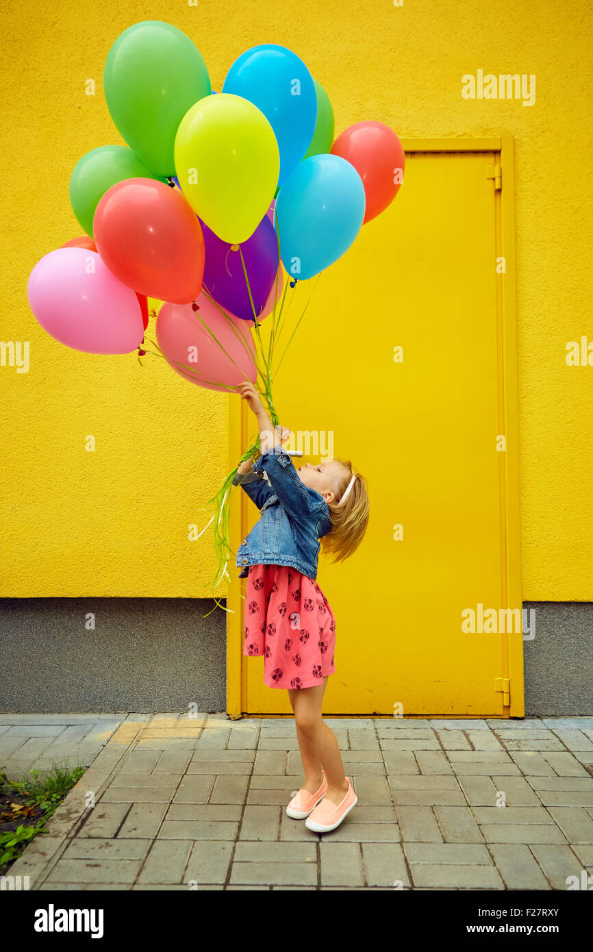 Happy little girl outdoors with balloons Photo Stock